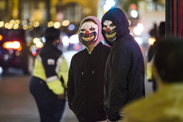 Two men with creepy clown masks for Halloween in the Georgetown neighborhood of Washington, USA on October 31, 2015. (Photo by Samuel Corum/Anadolu Agency/Getty Images)