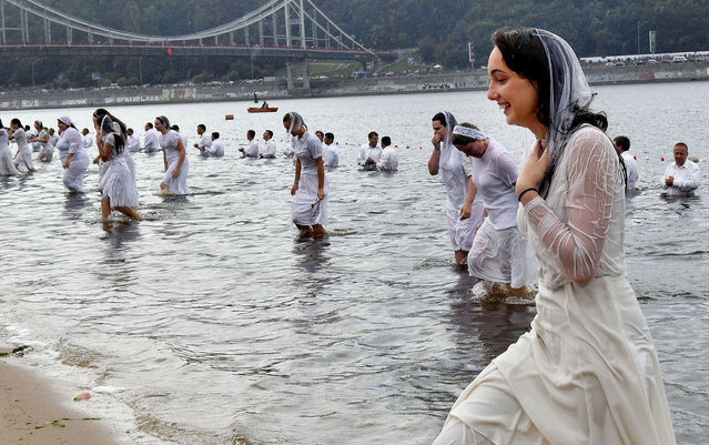 Ukrainian Evangelical Protestants take part in a mass baptism in the river Dniper in Kiev on July 22, 2018. Ukrainian Evangelical Protestant churches held a large-scale baptism in the Dniper river waters of about 500 people to mark the 1030th anniversary of the Christianization of the Kievan Rus. (Photo by Sergei Supinsky/AFP Photo)