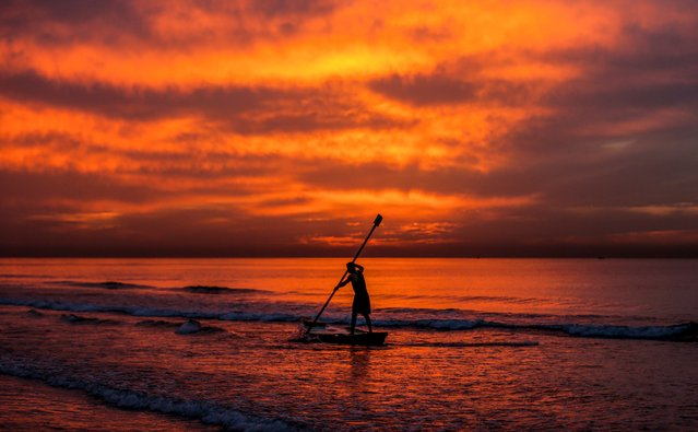 A Palestinian fisherman paddles his boat at sunset off the coast of Gaza City on December 27, 2017. (Photo by Mahmud Hams/AFP Photo)