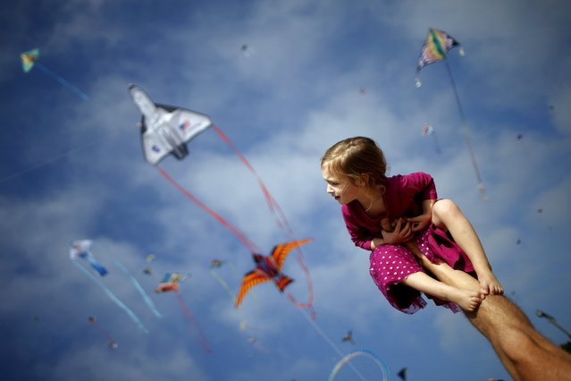 Madeleine Klonoski, 2, sits on her father's leg at a kite festival in Redondo Beach, California, United States, March 8, 2015. (Photo by Lucy Nicholson/Reuters)
