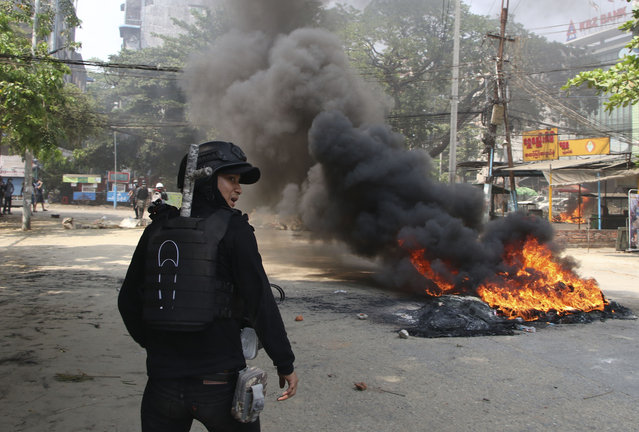 An anti-coup protester stands near a fire during a demonstration in Yangon, Myanmar, Saturday, March 27, 2021. As Myanmar's military celebrated the annual Armed Forces Day holiday with a parade Saturday in the country's capital, soldiers and police elsewhere reportedly killed dozens of people as they suppressed protests in the deadliest bloodletting since last month's coup. (Photo by AP Photo/Stringer)