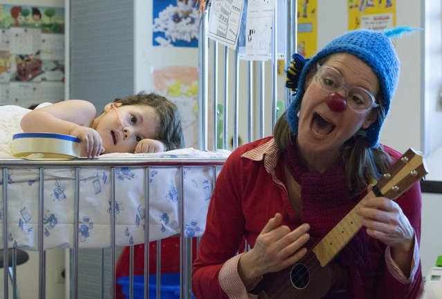 Mohamed, 5, watches as Belgian clown Jupette plays guitar at the pediatric department of the Hopital Erasme at the Universite Libre de Bruxelles (ULB), in Brussels January 27, 2015. (Photo by Yves Herman/Reuters)