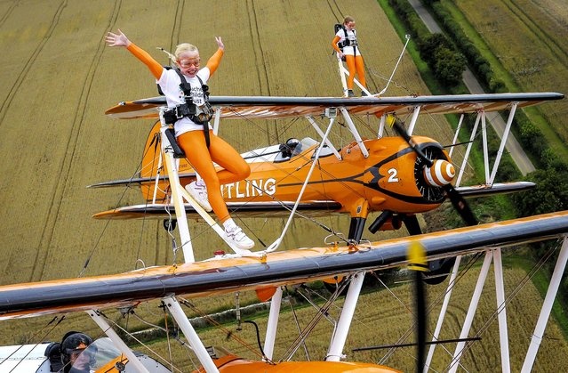 Nine-year-old cousins Rose Brewer and Flame Brewer wing walk over Rendcomb airfield in Cirencester, England, to  become the world's youngest formation wing walkers, on August 21, 2013. The two girls were inspired to break the record after reading about the plight of Eli Crossley who suffers from Duchenne Muscular Dystrophy. (Photo by Tim Ireland/Pool)