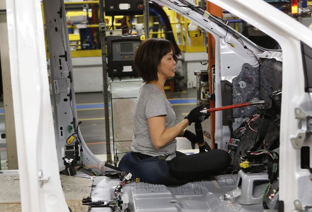 A Fiat Chrysler assembly worker works on the interior of a partially assembled minivan at the Windsor Assembly Plant in Windsor, Ontario, February 9, 2015. (Photo by Rebecca Cook/Reuters)