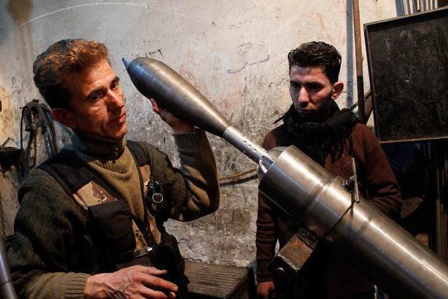"""A """"Free Syrian Army"""" fighter holds an improvised mortar shell inside a factory which previously manufactured steel and iron in Aleppo February 18, 2013. (Photo by Hamid Khatib/Reuters)"""
