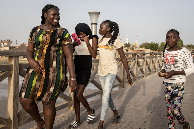 Young girls walk along a bridge from the Island of Fadiouth, Senegal on April 3, 2021. (Photo by John Wessels/AFP Photo)