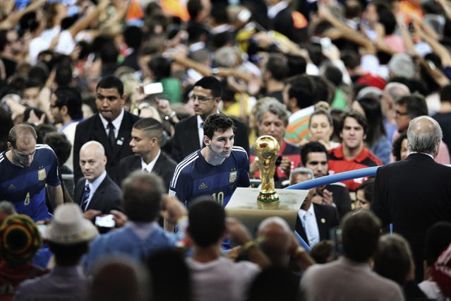 Bao Tailiang, a Chinese photographer of Chengdu Economic Daily, won the First Prize in the Sports Category, Singles, of the 2015 World Press Photo contest with this picture of Argentina's player Lionel Messi coming to face with the World Cup trophy during the final celebrations at Maracana Stadium in Rio de Janeiro, in this picture taken July 13, 2014, and released by the World Press Photo on February 12, 2015. (Photo by Bao Tailiang/Reuters/Chengdu Economic Daily/World Press Photo)
