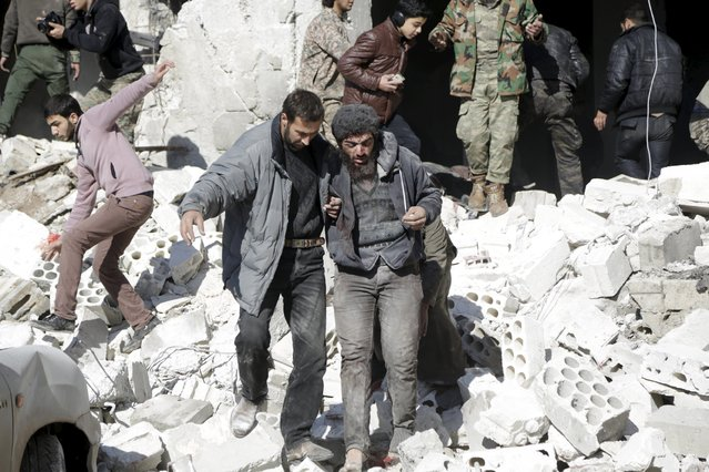 A resident helps an injured man in a site hit by what activists said were airstrikes carried out by the Russian air force in the rebel-controlled area of Maaret al-Numan town in Idlib province, Syria January 9, 2016. (Photo by Khalil Ashawi/Reuters)