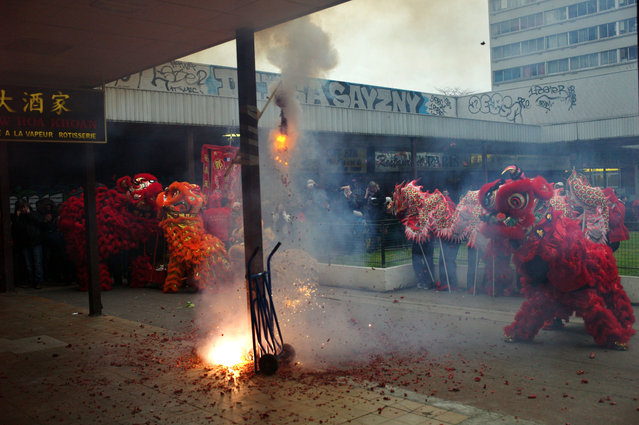 Firecrackers explode as Lion dancers perform in front of a restaurant at the Chinatown district of Paris, to celebrate the Chinese New Year, in Paris, Thursday, February 19, 2015. (Photo by Thibault Camus/AP Photo)