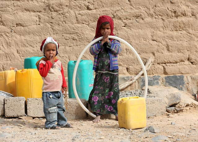 A girl and a boy wait to fill jerrycans with water at a public tap in Al Khurais village of Nihm district east of the capital Sanaa January 11, 2016. (Photo by Ali Owidha/Reuters)