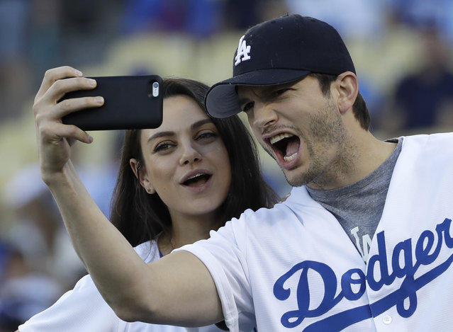 In this October 19, 2016, file photo, Ashton Kutcher and wife Mila Kunis take a selfie before Game 4 of the National League baseball championship series between the Chicago Cubs and the Los Angeles Dodgers in Los Angeles. Kunis and Kutcher are parents for the second time. A publicist for the actress said in an email Thursday, Dec. 1, that Kunis had given birth. (Photo by David J. Phillip/AP Photo)