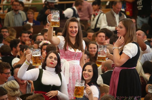 Visitors toast with beers during the opening day of the 185th Oktoberfest in Munich, Germany September 22, 2018. (Photo by Michael Dalder/Reuters)