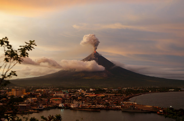 The Mayon volcano continues to erupt as the sun sets behind Legazpi city, Thursday, January 25, 2018 in Albay province, roughly 340 kilometers, (200 miles) southeast of Manila, Philippines. (Photo by Bullit Marquez/AP Photo)