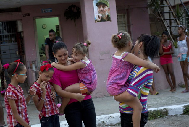 In this September 23, 2013 photo, from left to right, nine-year-old twins Camila and Carla Rodriguez, and 18-year-old twins Kamar and Sahar Youssef holding six-year-old twins Asley and Aslen Velazquez, pose for portraits along their street where a poster of Fidel Castro hangs in Havana, Cuba. The twins are just some of the 12 sets of twins living along two consecutive blocks in western Havana. (Photo by Ramon Espinosa/AP Photo)