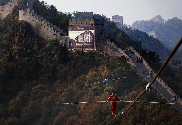 """Adili Wuxor (front), who is known as """"Prince of the Tightrope"""", and his apprentice walk on a tightrope above the Great Wall in Tianjin, on Oktober 18, 2013. (Photo by China Daily)"""