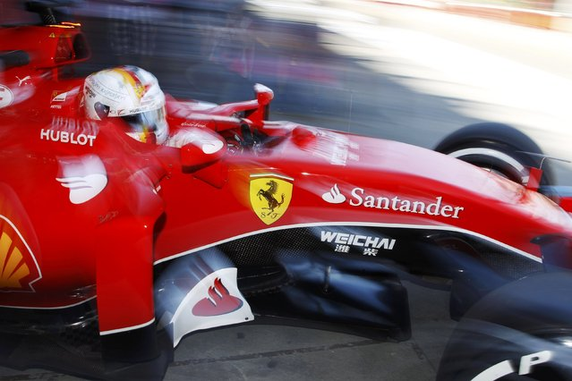 Ferrari Formula One driver Sebastian Vettel of Germany exits the team garage during the first practice session of the Australian F1 Grand Prix at the Albert Park circuit in Melbourne March 13, 2015. REUTERS/Brandon Malone