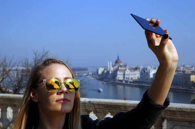 A woman watches a partial solar eclipse through a dark glass plate in Budapest March 20, 2015. A solar eclipse swept across the Atlantic Ocean on Friday with the moon set to block out the sun for about 2-1/2-hour, sky gazers in Europe, Africa and Asia getting a partial celestial show. (Photo by Laszlo Balogh/Reuters)