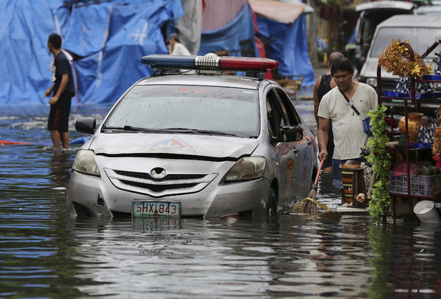 A police car is parked along a flooded street caused by rains from Typhoon Nock-Ten as vendors selling handicrafts including Christmas decorations clean rubbish in Quezon city, north of Manila, Philippines on Monday, December 26, 2016. (Photo by Aaron Favila/AP Photo)