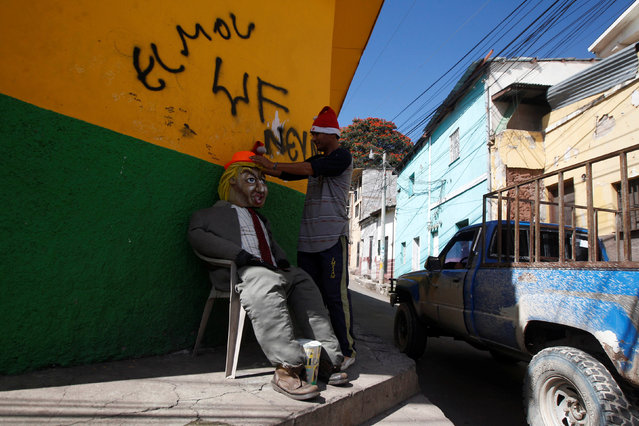 A man puts a hat on an effigy of U.S. President-elect Donald Trump, which will be burnt during a local New Year's Eve celebration, at La Leona neighborhood in Tegucigalpa, Honduras, December 27, 2016. (Photo by Jorge Cabrera/Reuters)