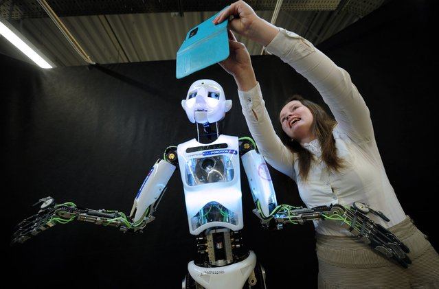 "A girl takes a selfie with a life-sized humanoid robot named ""RoboThespian"" at the Ball of Robots exhibition in Minsk, Belarus, March 17, 2015. (Photo by Sergei Gapon/AFP/Getty Images)"