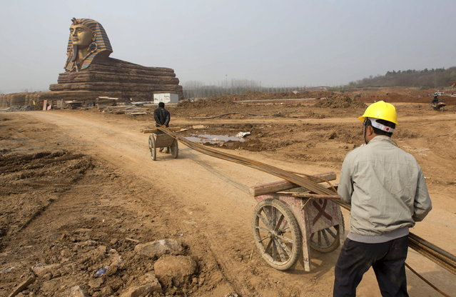 Labourers transport steel bars toward a full-scale replica of the Sphinx at an unfinished movie and animation tourism theme park, in Chuzhou, Anhui province, March 28, 2015. (Photo by Reuters/China Daily)