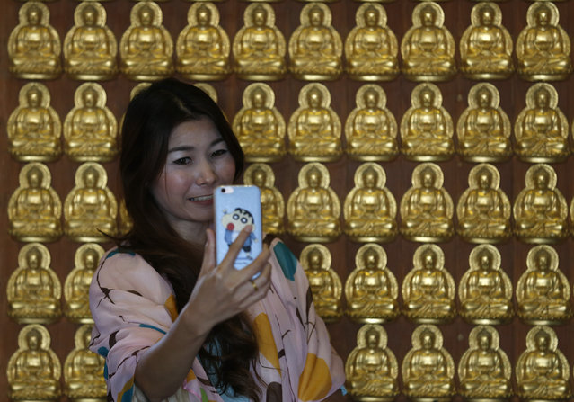"""A woman takes a """"selfie"""" at a temple to celebrate Chinese New Year in Nonthaburi province, on the outskirts of Bangkok, Thailand February 8, 2016. (Photo by Chaiwat Subprasom/Reuters)"""