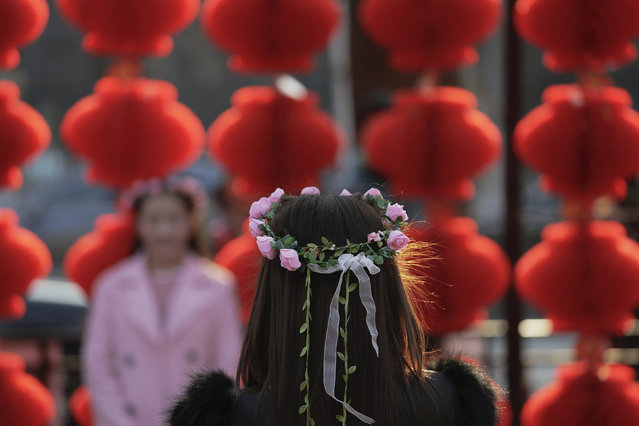 A woman is having her picture taken at the Longtan park as the Chinese Lunar New Year, which welcomes the Year of the Monkey, is celebrated in Beijing, China February 9, 2016. (Photo by Damir Sagolj/Reuters)