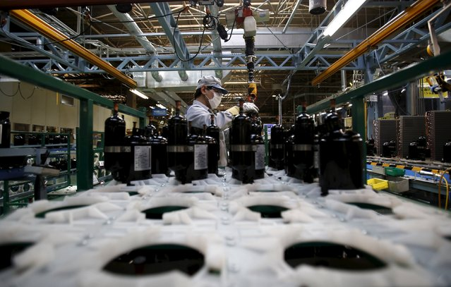 A Daikin Industries Ltd employee carries a tank filled with a refrigerant, low in global warming coefficiency, at the production line of outdoor air conditioning units at the company's Kusatsu factory in Shiga prefecture, western Japan March 20, 2015. (Photo by Yuya Shino/Reuters)