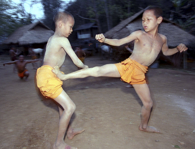 In this March 19, 2002, file photo, two novice Buddhist monks practice Muay Thai (Thai kickboxing) during a morning training session at the Golden Horse Monastery in northern Thailand. The death of a 13-year-old boy who was knocked out during a Muay Thai boxing match in Thailand has sparked debate over whether to ban child boxing. (Photo by David Longstreath/AP Photo)