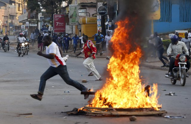 A supporter of Uganda's leading opposition party Forum for Democratic Change runs past burning objects as police and military forces disperse their procession with their presidential candidate to a campaign ground, in Kampala, Uganda, February 15, 2016. (Photo by James Akena/Reuters)