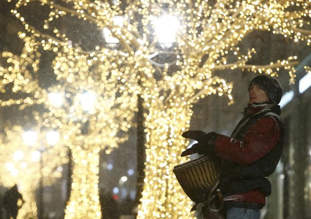 A musician beats the Conga drum, which is also known as Tumbadora, in a street decorated with festive installations and illumination lights during a snowfall in central Moscow, Russia, January 12, 2017. (Photo by Sergei Karpukhin/Reuters)