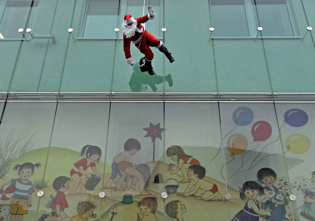 A member of the special police force dressed in a Santa suit descends from the roof of a paediatric clinic in Ljubljana, Slovenia, as part of a Christmas performance for patients of the clinic on December 18, 2013. (Photo by Srdjan Zivulovic/Reuters)