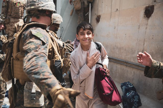 A boy is processed through an Evacuee Control Checkpoint (ECC) during an evacuation at Hamid Karzai International Airport, Kabul, Afghanistan on August 18, 2021. (Photo by Staff Sgt. Victor Mancilla/U.S. Marine Corps/Handout via Reuters)