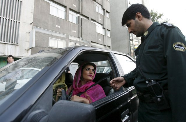 "A policeman asks a woman wearing bright coloured clothes for her identification papers at a morals police checkpoint in Tehran in this June 16, 2008 file photo. A new smartphone application that helps Iranians dodge the Islamic Republic's ""morality police"" is proving popular with the young, tech-savvy population but has quickly fallen foul of the authorities. (Photo by Reuters/Stringer)"