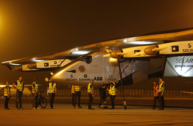 Ground staff prepare to push the Solar Impulse 2, a solar powered plane, into a hangar after it landed at the airport in the western Indian city of Ahmedabad, March 11, 2015. (Photo by Amit Dave/Reuters)