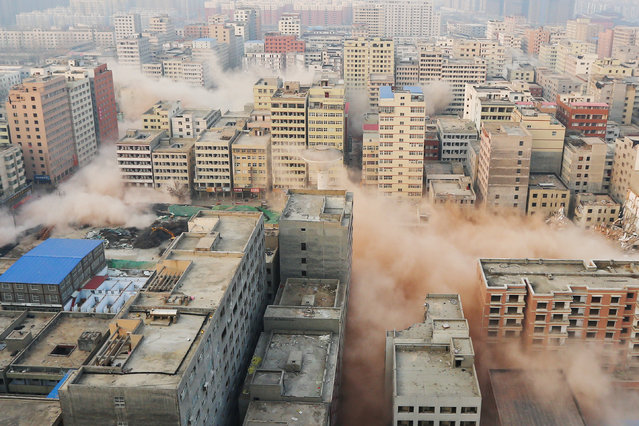 Smokes rising as buildings crumble during controlled demolition of an urban village in Zhengzhou, Henan province, China, January 23, 2017. (Photo by Reuters/Stringer)