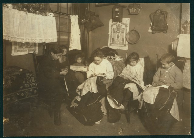 The Onofrio Cottone family finish garments in a tenement in New York, January 1913, in this Library of Congress handout photo. The three oldest children Joseph, 14, Andrew, 10, and Rosie, 7, help their mother sew garments and together they make about $2 a week when work is plenty. (Photo by Reuters/Bain Collection/Library of Congress)