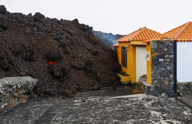 Lava reaches a house following the eruption of a volcano in the Cumbre Vieja national park, in the residential area of Los Campitos at Los Llanos de Aridane, on the Canary Island of La Palma, September 20, 2021. (Photo by Borja Suarez/Reuters)