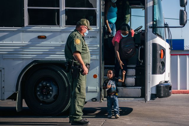 Migrants exit a Border Patrol bus and prepare to be received by the Val Verde Humanitarian Coalition after crossing the Rio Grande on September 22, 2021 in Del Rio, Texas. Thousands of immigrants, mostly from Haiti, seeking asylum have crossed the Rio Grande into the United States. Families are living in makeshift tents under the international bridge while waiting to be processed into the system. U.S. immigration authorities have been deporting planeloads of migrants directly to Haiti while others have crossed the Rio Grande back into Mexico. (Photo by Brandon Bell/Getty Images)