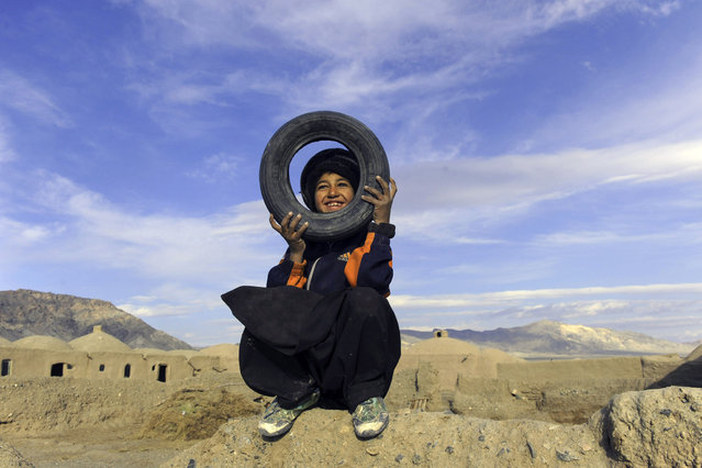 An Afghan child plays in the outskirts of Herat on January 23, 2014. Economic development is considered a vital weapon to stop the country from sinking back into civil war and to stem Islamist extremism after 100,000 international combat troops pull out. (Photo by Aref Karimi/AFP Photo)