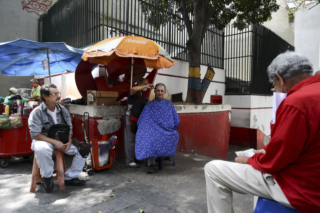 A woman cuts hair on a sidewalk as customers wait for their turn, in downtown Caracas, Venezuela, Wednesday, March 6, 2019. As the political and economic crisis deepens, the U.S., Germany and some 50 other countries consider Venezuela's President Nicolas Maduro's re-election invalid and have urged him to step aside so the country can prepare for elections. Maduro says he is the target of a U.S.-backed coup plot. (Photo by Eduardo Verdugo/AP Photo)