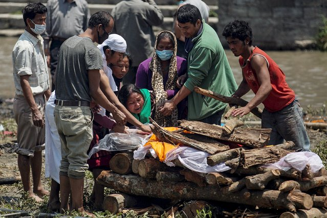 A woman cries as her father's body is prepared for cremation along a river, following Saturday's earthquake, in Kathmandu, Nepal, April 27, 2015. The man died during the 7.9 magnitude earthquake that hit the country on Saturday. (Photo by Danish Siddiqui/Reuters)