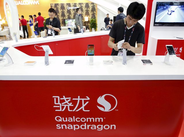 A staff displays a smartphone at Qualcomm's booth at the Global Mobile Internet Conference (GMIC) 2015 in Beijing, China, April 28, 2015. (Photo by Kim Kyung-Hoon/Reuters)