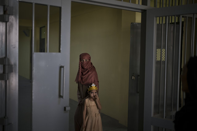 Razia and her six-year-old daughter Alia, stand inside the women's section of the Pul-e-Charkhi prison in Kabul, Afghanistan on September 28, 2021. When the Taliban took control of the northern city of Pul-e-Kumri the operator of the only women's shelter ran away, abandoning 20 women in it. When the Taliban arrived at the shelter the women were given two choices: return to their abusive families, or go with the Taliban. With nowhere to put the women, the Taliban took them to the abandoned women's section of Afghanistan's notorious Pul-e-Charkhi prison. (Photo by Felipe Dana/AP Photo)
