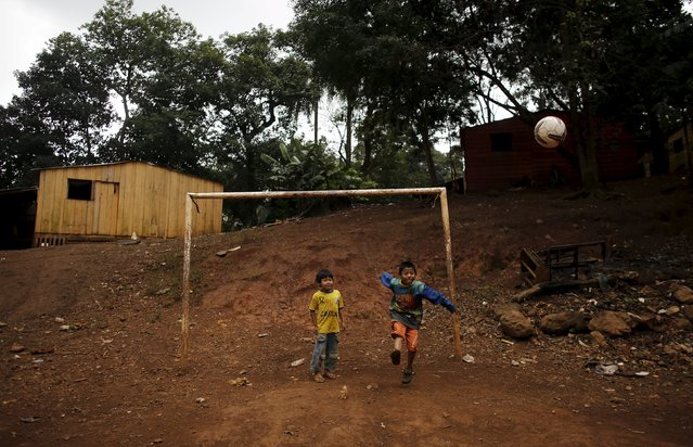 Guarani Indian boys play with a ball in the village of Pyau at Jaragua district, in Sao Paulo April 30, 2015. (Photo by Nacho Doce/Reuters)