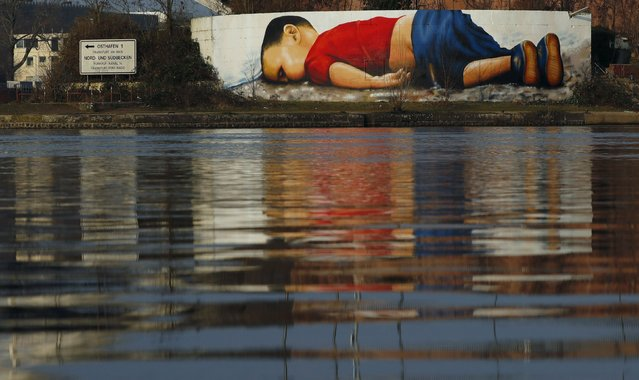 A huge graffiti artwork of toddler Aylan Kurdi, by Frankfurt artists Justus Becker and Oguz Sen is seen on a wall on the banks of river Main near the headquarters of the European Central Bank in Frankfurt, Germany, March 10, 2016. The huge graffiti image of toddler Aylan Kurdi, pictures of whose dead body stirred global sympathy for migrants fleeing war and poverty, confronts motorists, pedestrians and river travellers in Frankfurt. (Photo by Kai Pfaffenbach/Reuters)