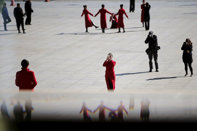 Hotel guides pose outside the Great Hall of the People during the third plenary session of the National People's Congress (NPC), in Beijing, China, March 13, 2016. (Photo by Damir Sagolj/Reuters)