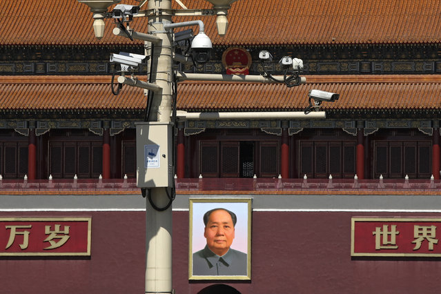 Surveillance cameras are mounted on a lamp post near the large portrait of Chinese leader Mao Zedong at the Tiananmen Gate in Beijing, Friday, March 15, 2019. Chinese Premier Li Keqiang on Friday denied Beijing tells its companies to spy abroad, refuting U.S. warnings that Chinese technology suppliers might be a security risk. (Photo by Andy Wong/AP Photo)