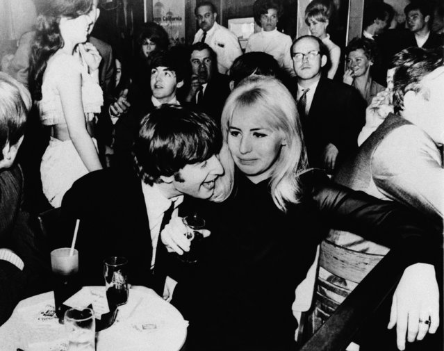 John Lennon, one of the Beatles, and his wife, Cynthia, are shown in a night spot after the visiting British Rock 'N' Rollers made their New York debut Sunday, February 11, 1964. Paul McCartney is behind Lennon. (Photo by AP Photo)