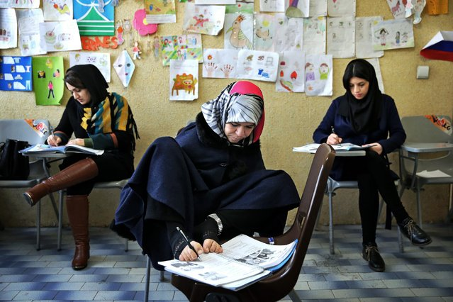 In this picture taken on Wednesday, March 11, 2015, Zohreh Etezadossaltaneh, center, who was born without arms, writes with her feet during an English language class, in Tehran, Iran. Now 52 years old, the retired Iranian teacher has dedicated herself to helping others with similar disabilities live full and satisfying lives. (Photo by Ebrahim Noroozi/AP Photo)